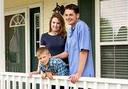 Small family on porch looking to sell their home
